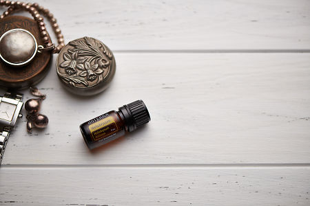 doTERRA Helichrysum, jewellery and trinkets on white rustic wooden background.
