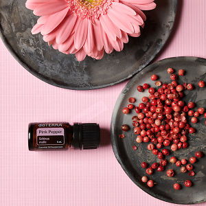 doTERRA Pink Pepper essential oil with pink peppercorns and a pink flower on separate ceramic plates on a pink textured background.