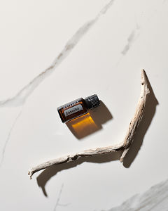 doTERRA Copaiba essential oil and driftwood on white marble in sunlight.