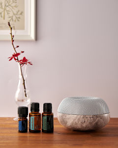 doTERRA Brevi Stone diffuser with Deep Blue, AromaTouch and Balance essential oils on a side table.