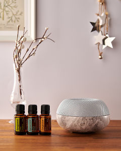 doTERRA Brevi Stone diffuser with Bergamot, Spearmint and Tangerine essential oils and holiday decorations on a side table.