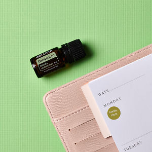 doTERRA Cardamom with an open pink diary on a green textured background.