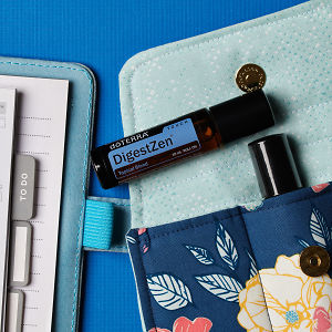 doTERRA DigestZen Touch on an essential oil bag with a diary on a blue textured background.
