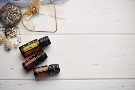 doTERRA Lemon, Cinnamon and Motivate oils with romantic jewellery on a white vintage wooden background.