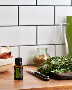 doTERRA Rosemary on a kitchen bench with fresh rosemary.