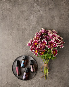 doTERRA Rose Touch, Ylang Ylang, Lavender and Geranium on a small ceramic plate with a bunch of flowers on a gray stone background.