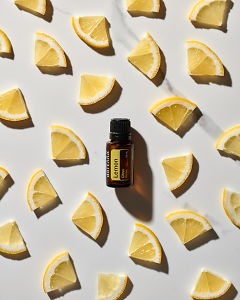 doTERRA Lemon essential oil and slices of lemon scattered on a white marble background.