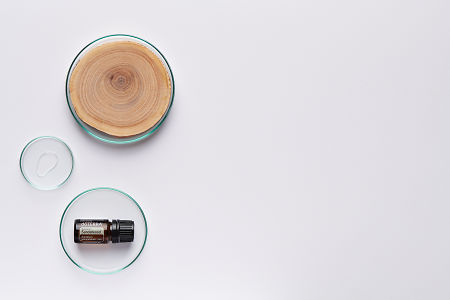 doTERRA Hawaiian Sandalwood in a petrie dish with sandalwood and oil in petri dishes on a white background.