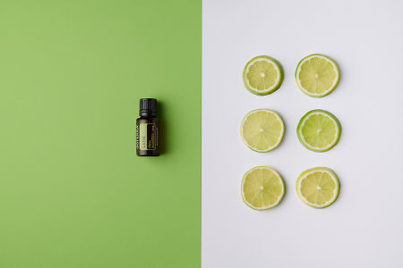doTERRA Lime oil on green background and lime slices on white background.