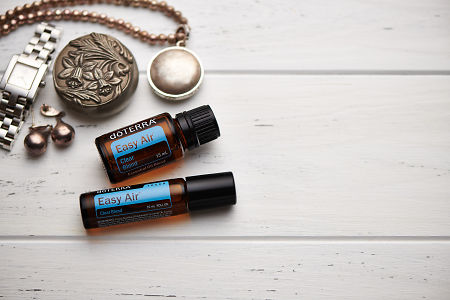 doTERRA Easy Air oil and Easy Air Touch blend, jewellery and trinkets on white rustic wooden background.