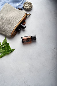 doTERRA Slim and Sassy with clutch, accessories and mint leaves on a white concrete background.