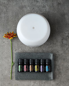 doTERRA Emotional Aromatherapy Starter Pack on a small gray towel with a flower on a gray stone background.
