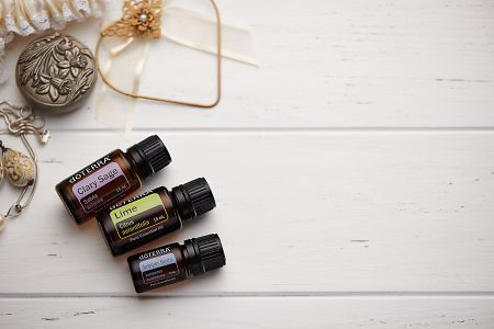 doTERRA Clary Sage, Lime and Juniper Berry oils and wedding accessories on white rustic wooden background.