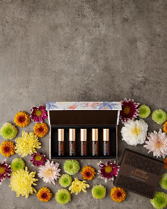 doTERRA Precious Florals Collection with scattered flowers on a gray stone background with copy space to add your message.