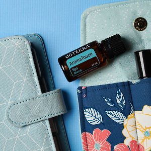 doTERRA Aroma Touch on an essential oil bag with a diary on a blue textured background.