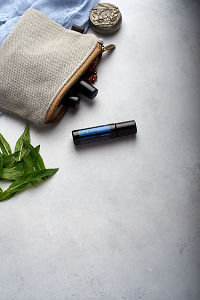 doTERRA Ice Blue Roll On with clutch, accessories and mint leaves on a white concrete background.