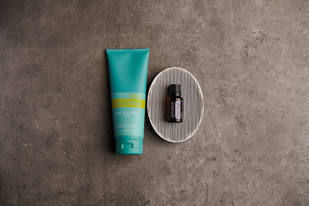 doTERRA Spa Hand and Body Lotion with Clary Sage essential oil on a gray soap dish on a stone background.