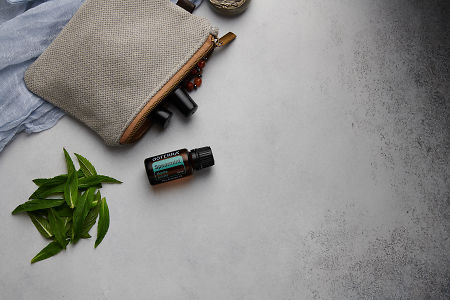 doTERRA Spearmint with clutch, accessories and mint leaves on a white concrete background.