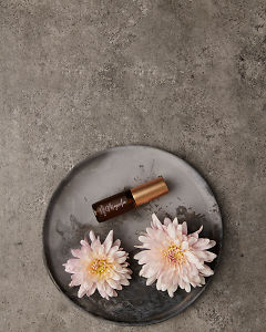 doTERRA Magnolia Touch 4ml on a ceramic plate with flowers on a gray stone background.