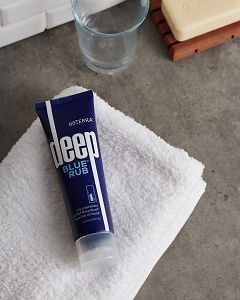 doTERRA Deep Blue Rub with a white fluffy towel on a gray stone bathroom bench top.