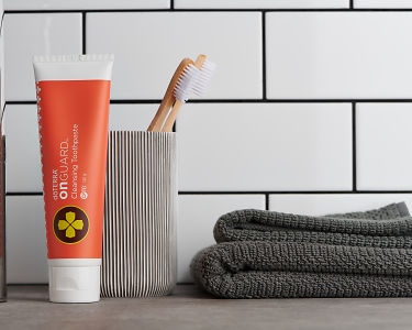 doTERRA On Guard Natural Cleansing Toothpaste and bathroom accessories on a bathroom vanity.