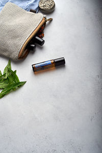 doTERRA DigestZen Touch with clutch, accessories and mint leaves on a white concrete background.