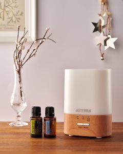 doTERRA Lumo diffuser with Bergamot and Peppermint essential oils and holiday decorations on a side table.