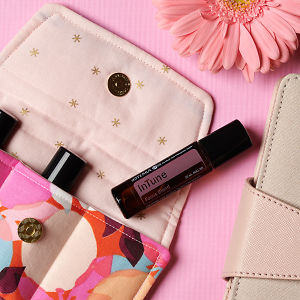 doTERRA InTune on an essential oil bag with a pink flower and diary on a pink textured background.