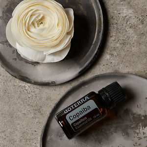 doTERRA Copaiba and a white flower on a ceramic plate on a grey stone background.