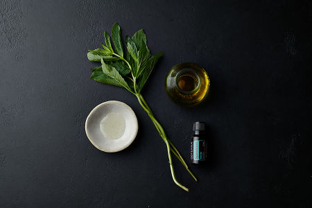 doTERRA Spearmint with a jar, bowl and mint branch on a black stone background.