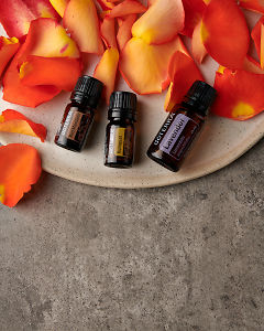 doTERRA Red Mandarin, Kumquat and Lavender with rose petals on a ceramic plate on a gray stone background.
