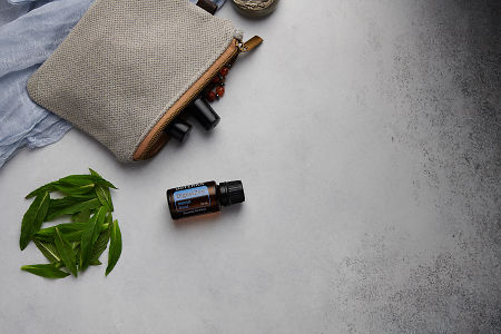 doTERRA DigestZen with clutch, accessories and mint leaves on a white concrete background.