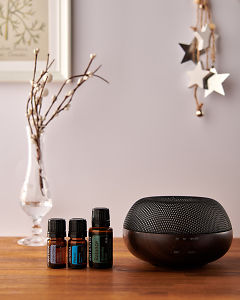 doTERRA Brevi Walnut diffuser with Juniper Berry, Peace and Balance essential oils and holiday decorations on a side table.