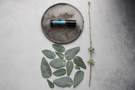 doTERRA Easy Air Touch on distressed ceramic plate with eucalyptus leaves on white concrete background.