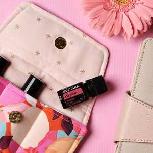 doTERRA Passion on an essential oil bag with a pink flower and diary on a pink textured background.