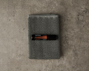 doTERRA Amavi Touch and gray washcloth on a gray stone background.