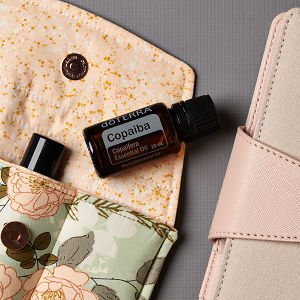 doTERRA Copaiba on an essential oil bag with a diary on a gray textured background.