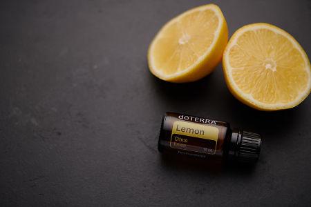doTERRA Lemon oil and lemon pieces on black concrete background.