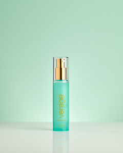 doTERRA Verage Moisturizer on a pale green background with reflection.