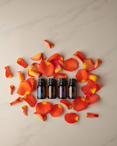 doTERRA Peppermint, Clove, Lavender and Grapefruit with rose petals on a white marble background.