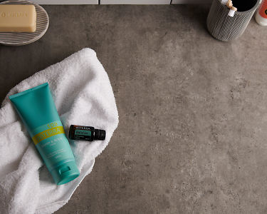 doTERRA Spa Hand and Body Lotion with Balance essential oil blend and bathroom accessories on a white towel on a stone background.