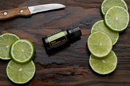 doTERRA Lime oil, lime slices and knife on rustic wooden chopping board.