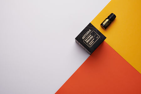 doTERRA Manuka and product box on yellow, orange and white geometric background.