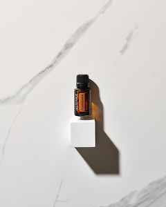 doTERRA Frankincense essential oil above a white block in sunlight on a white marble background.