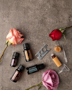 doTERRA Pink Pepper, Grapefruit, Tangerine and Siberian Fir with an oil key, pipette, funnel and roller bottle and scattered roses on a gray stone background.