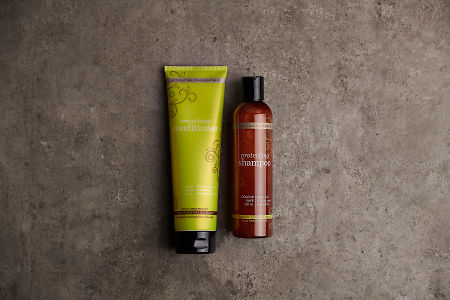 doTERRA Salon Essentials Shampoo and Conditioner on a gray stone bathroom bench.