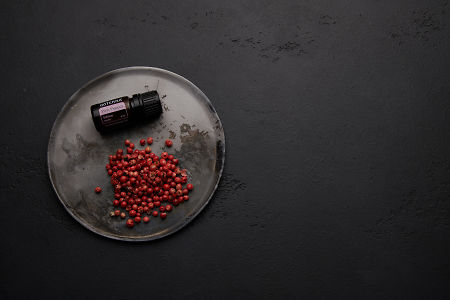 doTERRA Pink Pepper and pink peppercorns on a ceramic plate with a black concrete background.