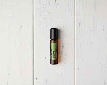 doTERRA Forgive Touch on a white wooden  background.