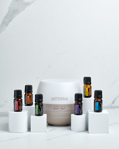 doTERRA Emotional Aromatherapy Starter Pack on white blocks on a white marble background.