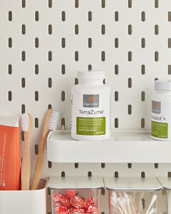 doTERRA TerraZyme on a bathroom shelf with additional doTERRA products and bathroom accessories.